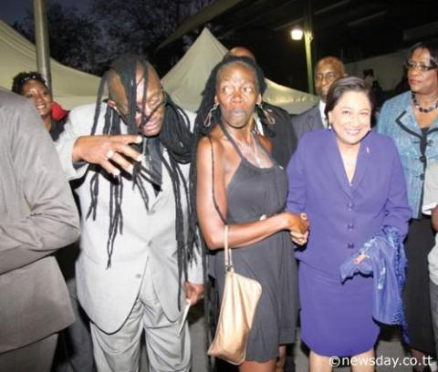 CLOWNING AROUND: Prime Minister Kamla Persad-Bissessar (right) laughs as Community Development Minister Winston 'Gypsy' Peters playfully 'wears' the dreadlocks of well-known community activist Christine 'Twiggy' Levia, centre, at yesterday's Hoop of Life awards ceremony at the St Barbs Basketball courts in Laventille.