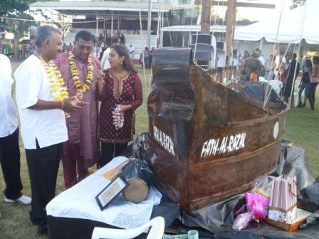 Couva South MP, Rudranath Indarsingh (left), Councillor Allan 'Taxi' Seepersad (2nd from left) and Couva North MP, Ramona Ramdial (right) discuss antique Indo-Trinidadian artifacts and the model of the Fath-al-Razak on display at the Couva Indian Arrival Celebration