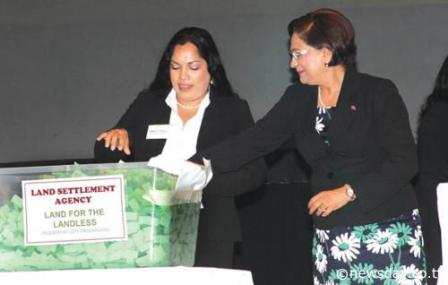First draw: An employee of Ernst & Young helps Prime Minister Kamla Persad-Bissessar make the first draw from 500 applicants to receive lots of land at Southern Academy for the Performing Arts, San Fernando yesterday. Author: ANIL RAMPERSAD