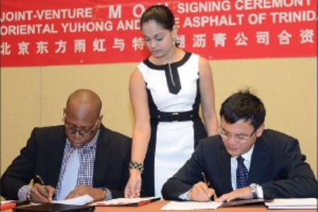 STRONGER TIES: Ashley Taylor, left, chairman of Lake Asphalt of Trinidad and Tobago, and Li Weiguo, chairman of Beijing Oriental Yuhong Waterproof Technology Company Ltd, sign a memorandum of understanding and confidentiality agreement between the companies during a ceremony at the Hyatt Regency (Trinidad), Port of Spain yesterday. Looking on is Lake Asphalt's corporate secretary Richelle Lyman. —Photo: CURTIS CHASE