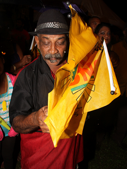 This man torches a UNC flag during the rally in Chaguanas on Friday night.