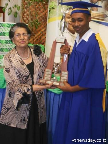 AWARD PRESENTATION: Lady Zalayhar Hassanali, widow of late president Noor Hassanali, presents the award to Most Outstanding Trainee of 2013, Joshua Sahadeo, right, who was also the valedictorian of 2013.