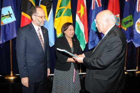 His Excellency José Miguel Insulza presents the report to Prime Minister Persad-Bissessar. Looking is Caricom Secretary General, Irwin LaRocque