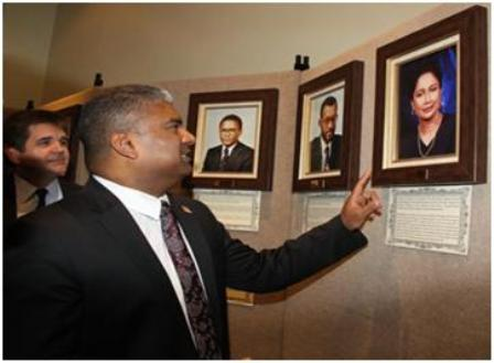 Attorney General Anand Ramlogan looks at a photograph of Prime Minister Kamla Persad-Bissessar during the commissioning ceremony of the law museum of T&T at the old Cabildo Building, Sackville Street, Port-of-Spain, yesterday. The photograph was taken when she was the attorney general in the Basdeo Panday-led UNC government. Photos: Trinidad Guardian