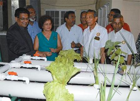 Food Production Minister Devant Maharaj, left, and members of the St Augustine Rotary Club look at the aquaponics system. Photo: Shastri Boodan