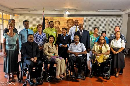 Prime Minister Kamla Persad-Bissessar poses for a photo with members of the Consortium of Disability Organisations in St Ann's today. PHOTO COURTESY THE OFFICE OF THE PRIME MINISTER.