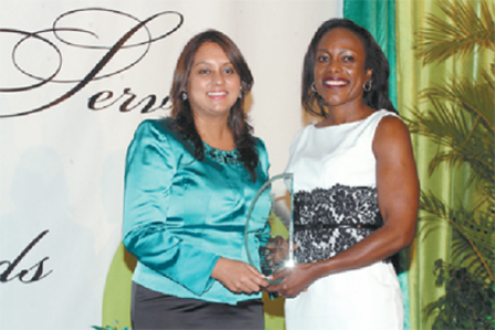 Ramona Ramdial, Minister of State in the Ministry of the Environment and Water Resources, left, presents the Green Leaf Award for Non-Governmental Organisation (NGO) to Stacey Ann Lewis, representing the Turtle Village Trust. PHOTO: SEAN NERO