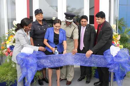 officially open: Prime Minister Kamla Persad-Bissessar, third left, cuts the ribbon to open the Piarco Police Station on Wednesday at Golden Grove Road, Piarco. Looking on from left are UdeCOTT managing director Jerlean John, acting sergeant Jennifer Crawford, acting Police Commissioner Stephen Williams, Housing Minister Dr Roodal Moonilal and Legal Affairs Minister Prakash Ramadhar. —Photo: STEPHEN DOOBAY