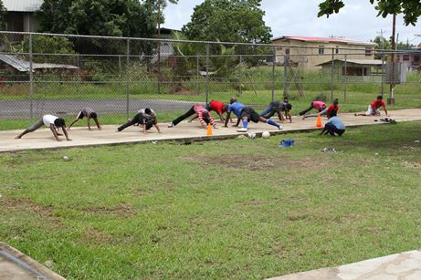 Participants performing stretching exercises during football training at the Bank Village Vacation Camp