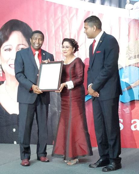 Prime Minister Kamla Persad-Bissessar SC, receives an award from Broward County Commissioner, Dale Holness, left, at a Republic Day dinner in South Miami, on Monday night. At right is T&T Consul General, Dr Anil Ramnanan.