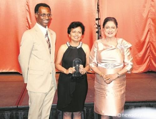 Prime Minister Kamla Persad-Bissessar, right, poses with Head of the Public Service Reynold Cooper after Mohandai Singh Maraj was presented with an award for her 41 years of working in the Public Service. The PM yesterday honoured retirees of the Office of the Prime Minister at the Hyatt Regency, Port-of-Spain.  Author: SUREASH CHOLAI