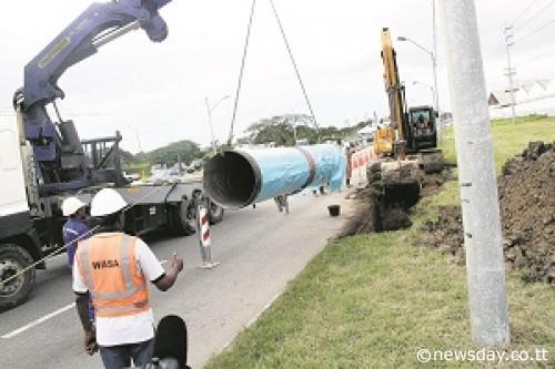 Pipe laying: Water and Sewerage Authority (WASA) workers laying down the first pipeline to mark the start of the Beetham Transmission Pipeline Project at the Beetham Highway on Monday. Author: SUREASH CHOLAI