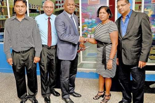 COLOURFUL ENDEAVOUR: Roger Roach, managing director of ANSA Coatings Ltd, centre, greets Micheal Ramsook, right, and his wife during the opening of the new Sissons Colour Shop in Debe on Tuesday. Looking on at left is Shiva Roopnarine, president of the Penal/Debe Chamber of Commerce, and Umanath Maharajh, commercial manager, Sissons Paints. --Photo: DEXTER PHILIP