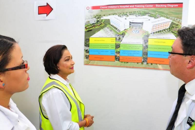 Former Prime Minister Kamla Persad-Bissessar looks at a Diagram of Couva Children's Hospital