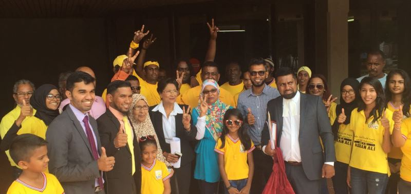 PHOTO -  Political Leader, Kamla Persad-Bissessar, SC together with attorney Saddam Hosein (from the left in grey suit), candidate Adrian Ali (dark suit and yellow tie), attorney Gerald Ramdeen (right) and UNC candidate Faaiq Mohammed (next to Gerald Ramdeen in blue shirt) celebrate with UNC supporters outside the Hall of Justice this morning (Sunday 27th November 2016)