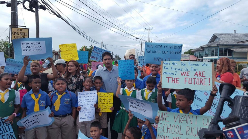 In pic Dr Roodal Moonilal and councillor Kumarie Kuarsingh join the children and staff of the Ramai trace Hindu school in protest.
